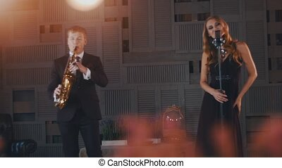 Jazz vocalist in black dress perform on stage at microphone with saxophonist.