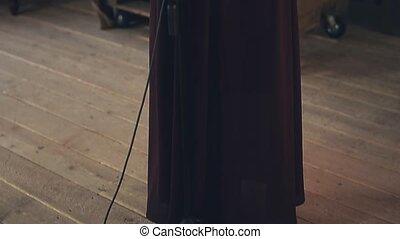 Jazz vocalist in dark elegant dress perform on stage at microphone. Dance.