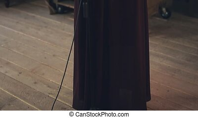 Jazz vocalist in dark elegant dress perform on stage at microphone. Dance.