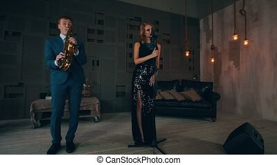 Jazz vocalist in glowing dress perform on stage with saxophonist. Live concert
