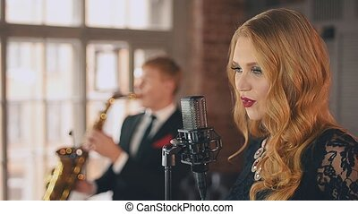 Jazz vocalist perform on stage with saxophonist. Duet. Music...