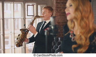 Jazz vocalist perform on stage with saxophonist. Song. Musicians. Live concert