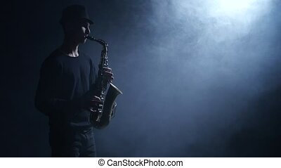 Jazzman performs composition on the saxophone. Smoke in the dark