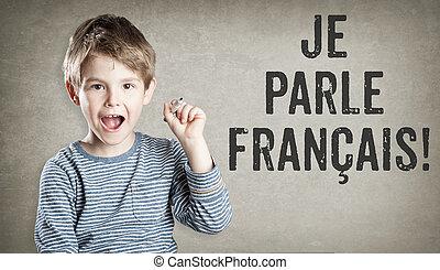 Boy says he speaks French, on grunge background, writing, amazed, copy space