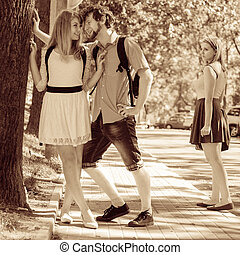 Jealous girl looking at flirting couple outdoor. Happy young...