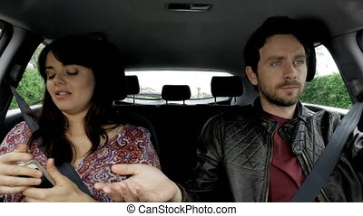 Jealous man in car checking cell phone of woman