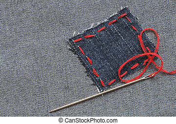 Jeans Patch - Needle and patch with red thread attached on...