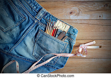 Jeans with measure and crayons, paintbrushs in back pocket on wooden