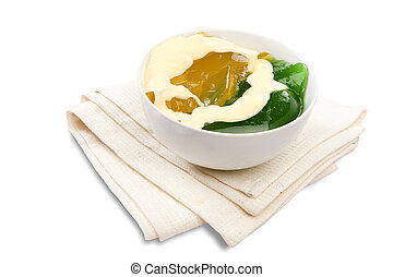 A bowl of green and yellow jelly with custard drizzled on top of it on an isolated white background