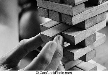 jenga blocks and hand - Wooden jenga block game of skill