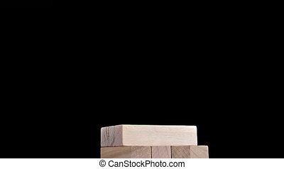 Jenga puzzles gather in tall tower. Stop motion, black background