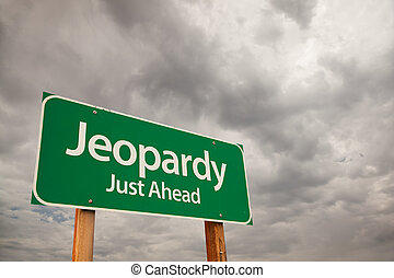 Jeopardy Just Ahead Green Road Sign with Dramatic Storm Clouds and Sky.