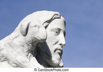 Jesus and the Lamb - A statue of Jesus and a lamb against a...