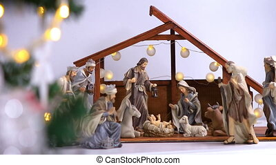 Jesus Christ Nativity scene near Christmas tree. Jesus Christ birth in a stable with Mary and Joseph figures. Christmas scene. Dolly shot zoom in 4k