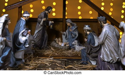 Jesus Christ Nativity scene with atmospheric lights. Jesus Christ birth in a stable with Mary and Joseph figures. Christmas scene. Dolly shot