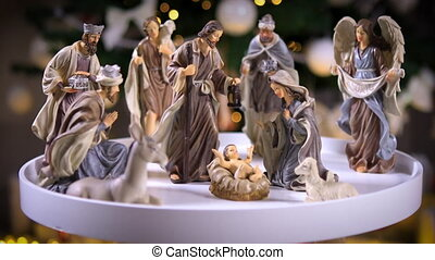 Jesus Christ Nativity scene with atmospheric lights in front of Christmas tree on white table. Christmas scene with figurines. Dolly shot 4k