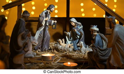 Jesus Christ Nativity scene with atmospheric lights and candles. Jesus Christ birth in a stable with Mary and Joseph figures. Christmas scene. Dolly shot