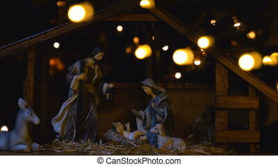 Jesus Christ Nativity scene with atmospheric lights. Jesus Christ birth in a stable with Mary and Joseph figures. Christmas scene.