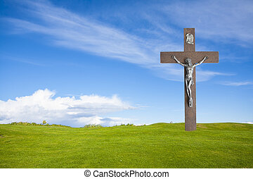 Jesus Christ on the cross and summer grass with blue sky