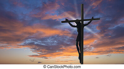 Jesus Christ on the Cross with sunset clouds as a background