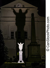 Jesus Christ statue behind St. Louis Cathedral in New Orleans, Louisiana by night