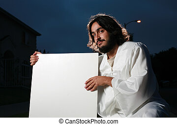 Jesus holding a blank white poster board outdoors at night