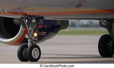 Jet aircraft moves on taxiway at airport. Landing gear,...
