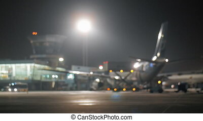 Wide shot of a jet airplane standing near the airport terminal at night