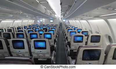 Jet airplane interior view economy class monitors on seats -...