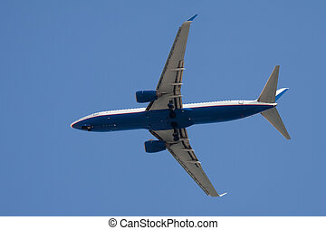 Jet airplane landing. On blue sky background