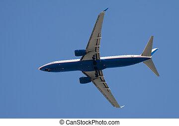 Jet airplane landing. On blue sky background