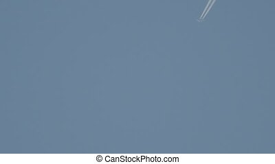Jet airplane with trail against the blue sky, blurry image...