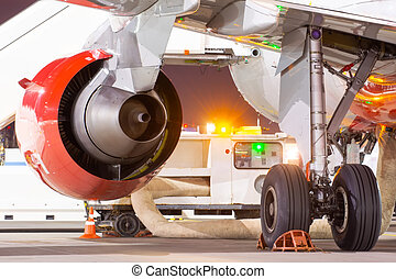Jet engine and main landing gear, rear view on the night apron of the airport.