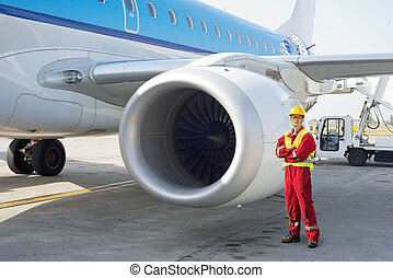 Jet engine mechanic posing next to a commercial aircraft on...