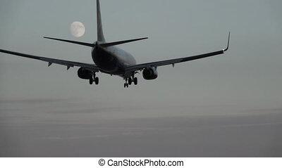 Jet landing at dusk against full moon, slow motion