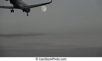 Jet landing at dusk against full moon, slow motion - Bottom...