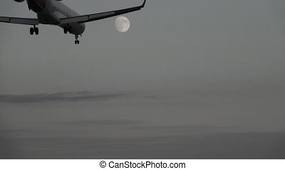 Jet landing at dusk against full moon, slow motion