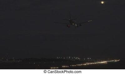 Jet landing at night against full moon - Bottom view of...
