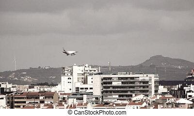 Jet landing behind buildings - Modern jet landing behind...