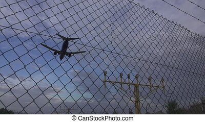 Jet landing in super slow motion behind airport railing -...