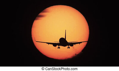 Jet landing with sun behind it - Silhouette of jumbo jet...