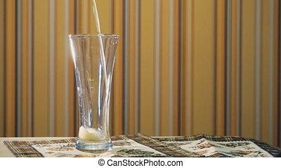 Jet of light beer fills a transparent glass