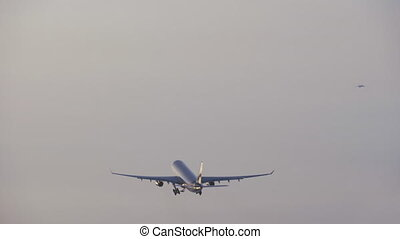 Wide shot of a jet plane flying through the gray sky and closing its landing gear