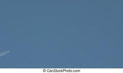 Jet plane flies in the blue sky, leaving a vapor trail. -...