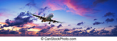 Jet plane is maneuvering for landing in a spectacular sunset sky. Panoramic composition.