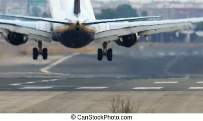 Jet plane landing with smoke on runway - Long shot of jet...