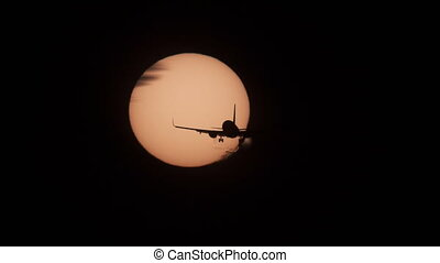 Jet plane landing with sun behind it, 4k - Silhouette of...