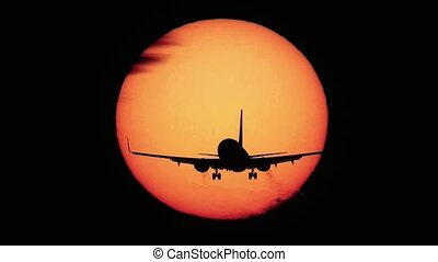 Jet plane landing with sun behind it - Silhouette of jumbo...
