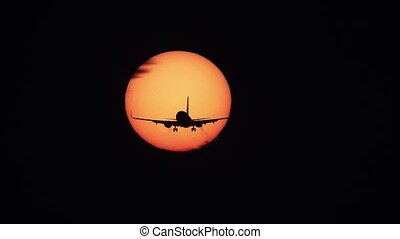 Jet plane landing with sun behind it, uhd version -...