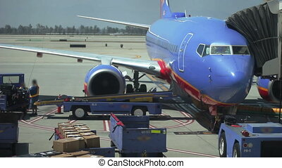 This is a shot at an airport in which workers are prepping a jet plane for take off.